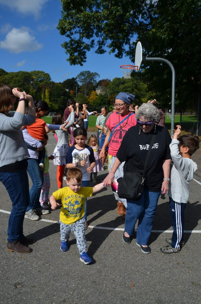Picture of two adults with two children walking through a group with raised arms.